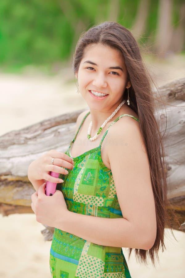 Schönes jugendlich Mädchen, welches das Mobiltelefon, lächelnd auf hawaiischem beac hält stockbilder