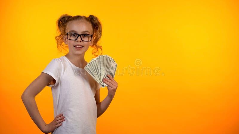 Schönes Jugendlicheholdingbündel Dollar, erstes Einkommen, gewinnende Lotterie lizenzfreie stockfotografie