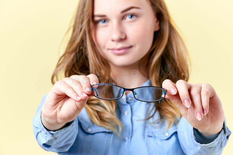 Schönes Jugendlichmädchen mit dem Ingwerhaar, Sommersprossen und blauen Augen, die Lesebrille halten und, junge Frau mit Schauspi lizenzfreie stockfotografie