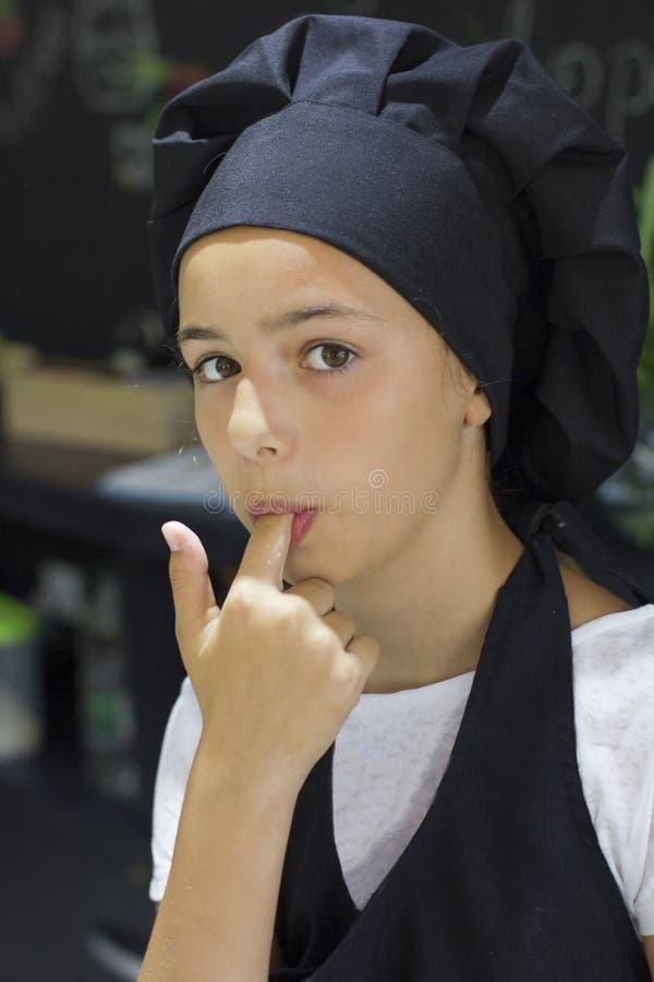 Schönes Jungekoch-Chefmädchen in einer schwarzen Chef ` s Kappe leckt eine Flosse lizenzfreie stockbilder