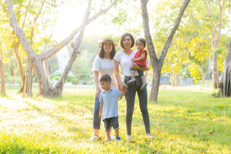 Schönes junges asiatisches Elternteilfamilien-Porträtpicknick im Park, im Kind oder in den Kindern und in der Mutterliebe glückli lizenzfreie stockfotografie