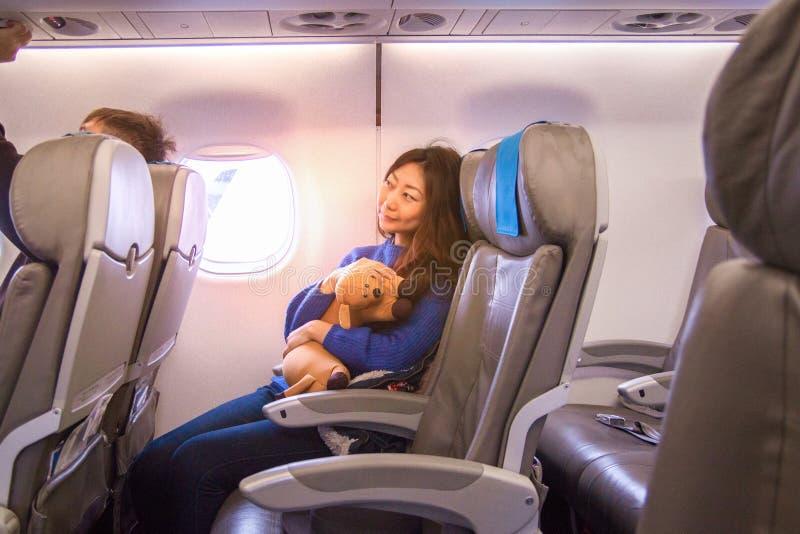 Schönes junges asiatisches Mädchen, das bequem auf dem Sitz sitzt und den Smartphone in der Kabine und im Lächeln betrachtet stockfotografie