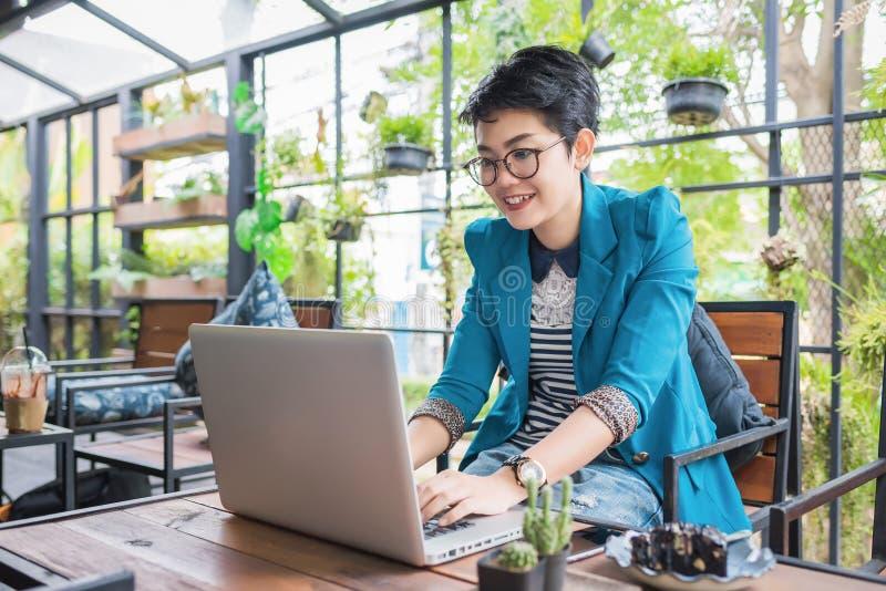 Schönes junges asiatisches Mädchen, das an einer Kaffeestube mit einem Laptop arbeitet stockfoto