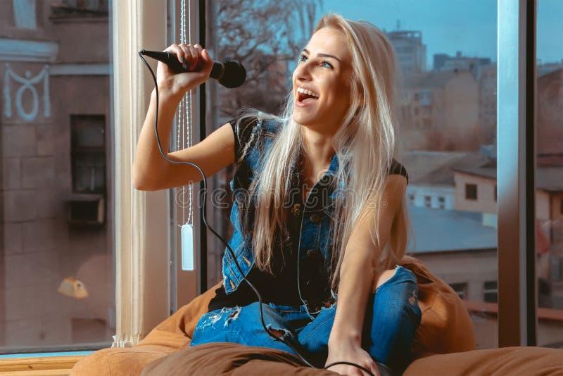 Schönes junges blondes Frauen-Gesangkaraoke mit einem Mikrofon stockbilder