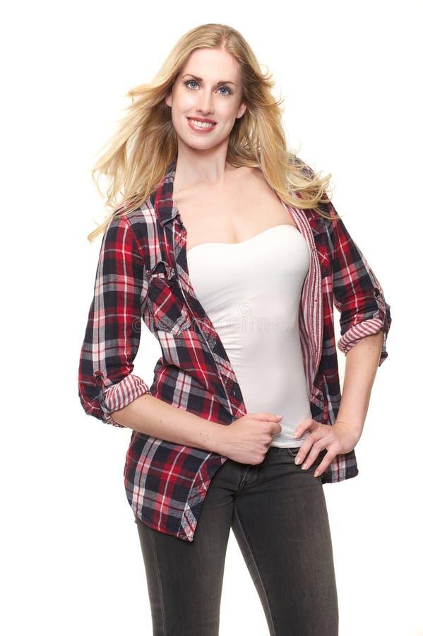 Schönes junges blondes Mädchen, das im Studio lächelt stockfoto