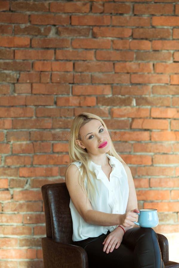 Schönes junges blondes Mädchen, das mit einer Schale sich entspannt stockfoto
