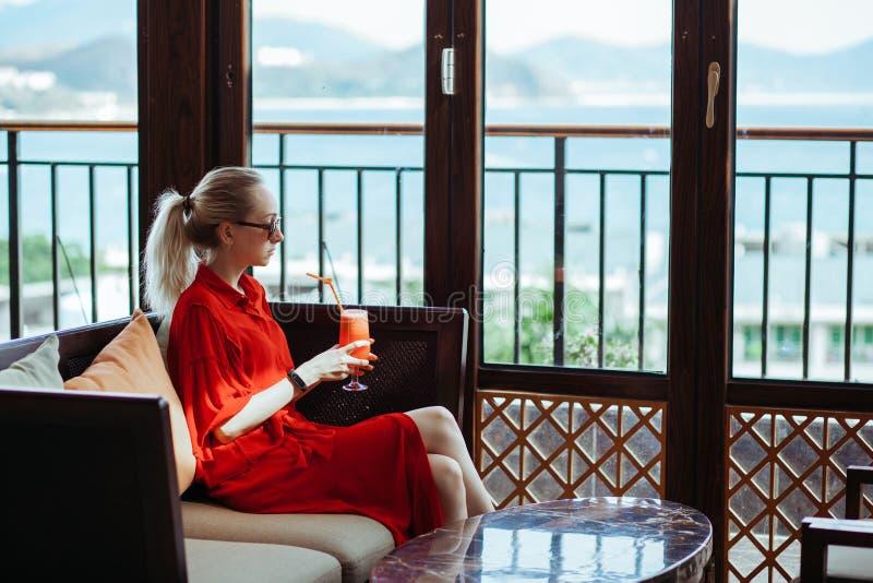 Schönes junges blondes Mädchen im roten Kleid und in der Sonnenbrille rotes Cocktail von einem Glas auf einer Freiterrasse von tr lizenzfreies stockbild