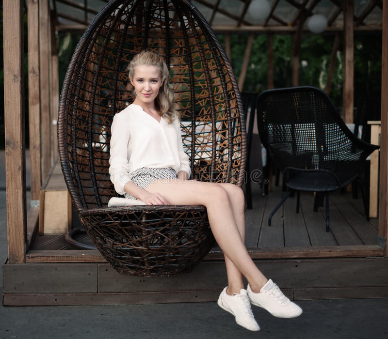 Schönes junges blondes Mädchen mit den langen Beinen, die in einem geflochtenen Stuhl an einem Café im Freien auf einem warmen So stockbild