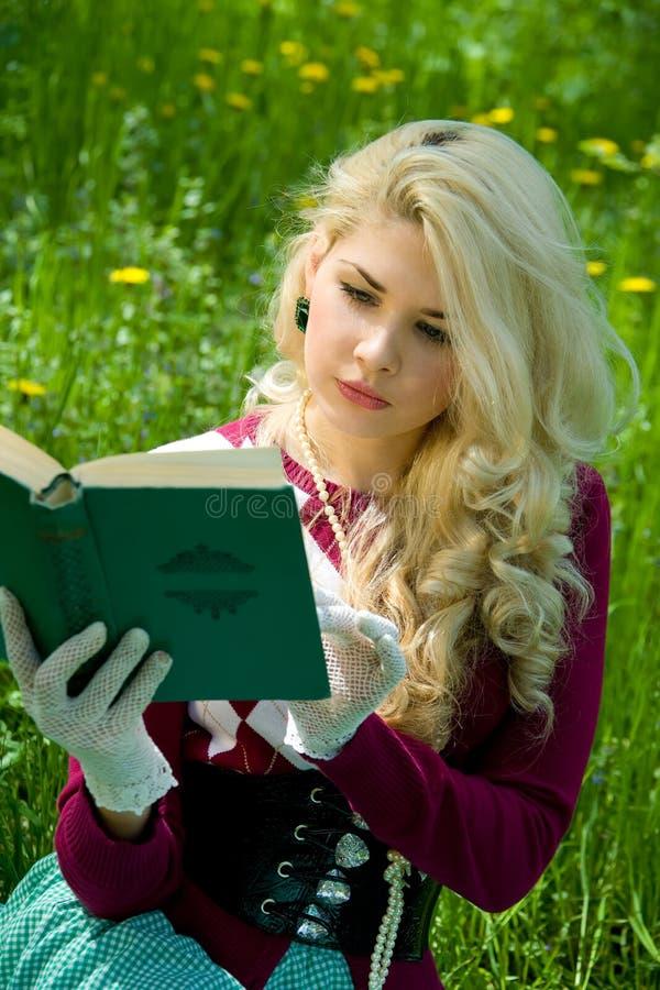 Schönes junges blondes mit Buch im Sommerpark lizenzfreies stockfoto