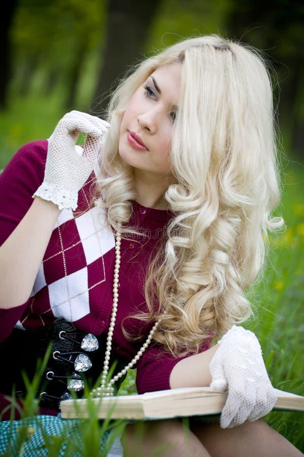 Schönes junges blondes mit Buch im Sommerpark stockfotografie
