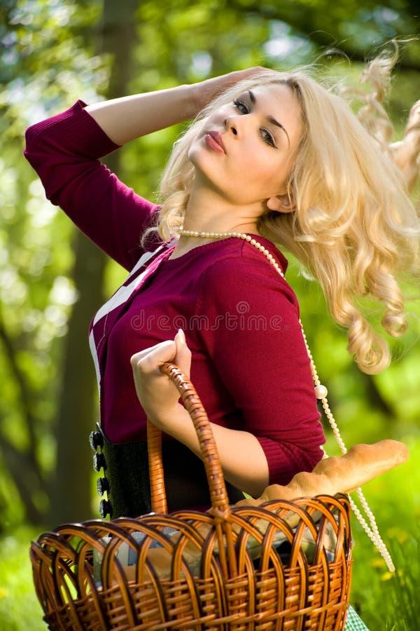 Schönes junges blondes mit Korb im Sommerpark stockfoto