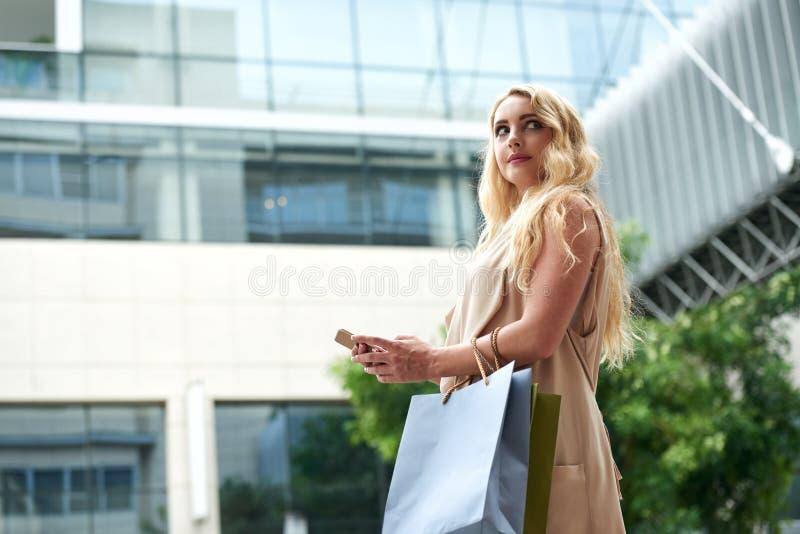 Schönes junges blondes unter Verwendung Smartphones in der Straße lizenzfreies stockfoto