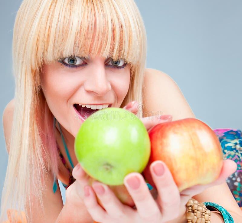 Schönes junges blondy mit frischem Apfel stockfoto
