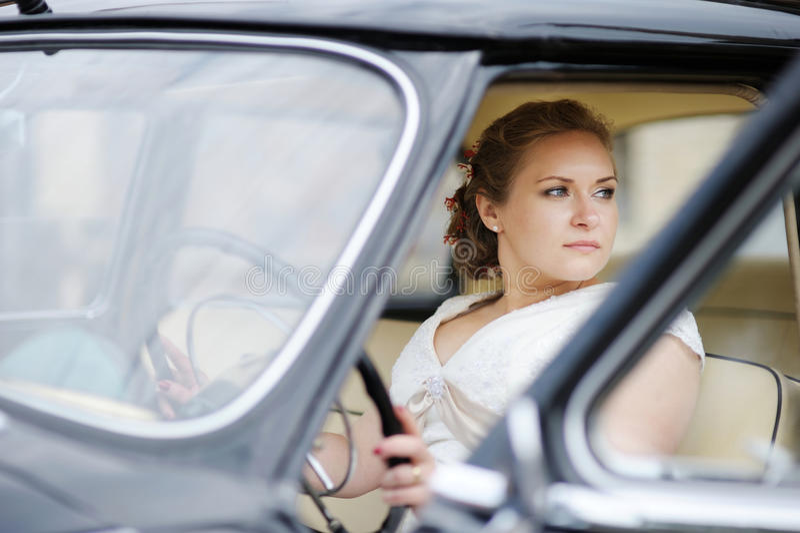 Schönes junges Brautporträt in einem Auto stockfoto