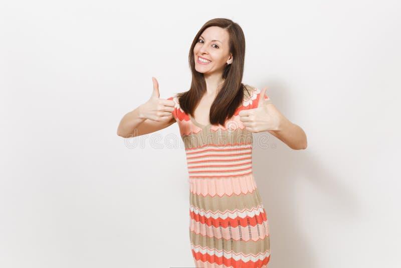 Schönes junges brunette Mädchen im hellen beige und rosa kopierten Kleid freut sich, oben Gestendaumen herein lächeln und Show stockfotos