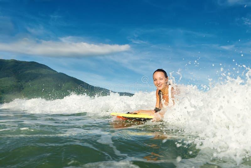 Schönes junges Brunettefrauenschwimmen auf Surfbrett mit nettem Lächeln lizenzfreie stockfotografie