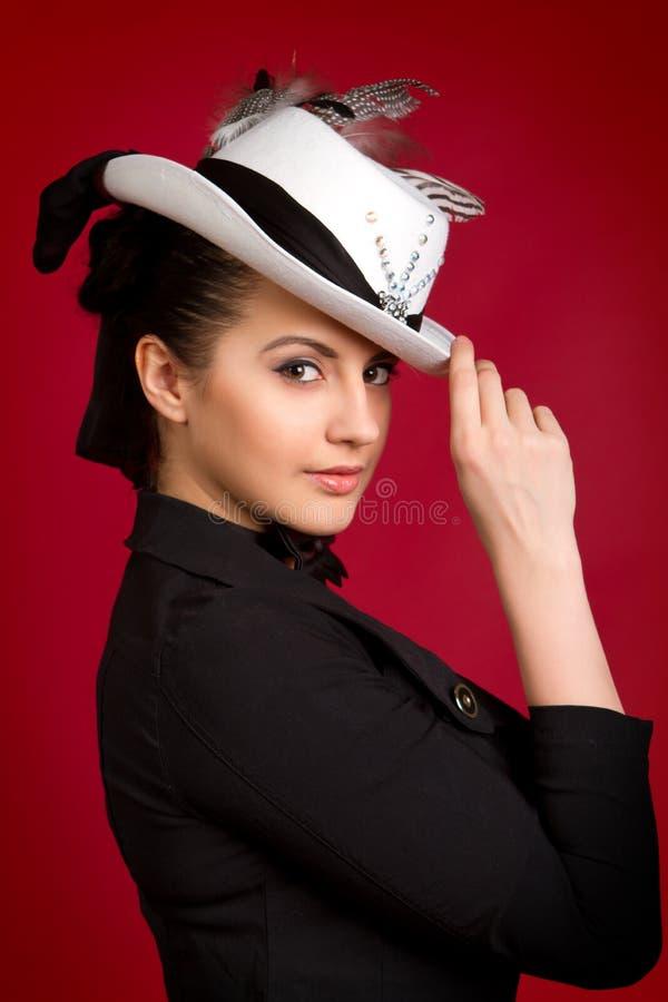 Schönes junges Brunettemädchen in einem weißen Hut auf einem roten Hintergrund lizenzfreies stockfoto