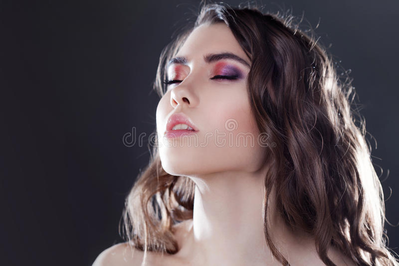 Schönes junges Brunettemädchen mit dem langen gewellten Haar Gelockte Frisur Schwarzer Hintergrund lizenzfreie stockfotografie