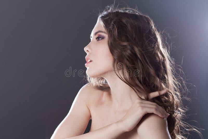 Schönes junges Brunettemädchen mit dem langen gewellten Haar Gelockte Frisur Schwarzer Hintergrund lizenzfreie stockfotos