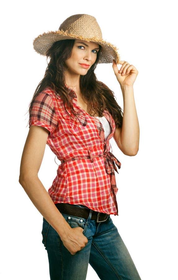 Schönes junges Cowgirl, das einen Hut trägt stockfotografie