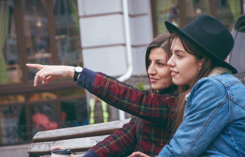 Schönes junges Europäerinnen bespricht, was auf der Bank im Hintergrund der Stadt geschieht lizenzfreies stockbild