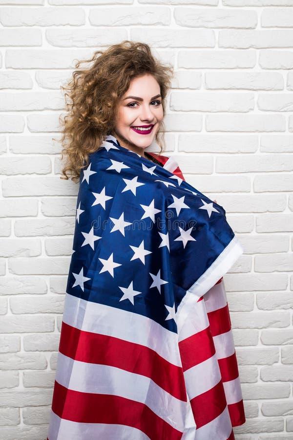 Schönes junges gelocktes Mädchen in der zufälligen Kleidung, die, stehend mit amerikanischer Flagge gegen Backsteinmauer aufwirft stockbilder