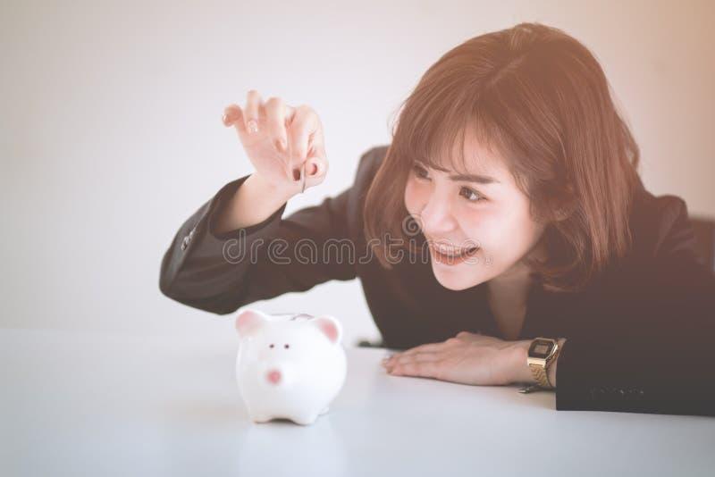 Schönes junges Geschäftsmädchen-Einsparungsgeld lizenzfreie stockfotografie