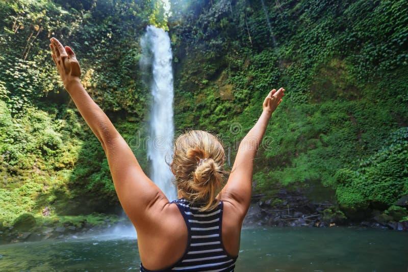 Schönes junges glückliches Mädchen, das Natur unter tropischem frischem Wasserfall genießt stockfoto