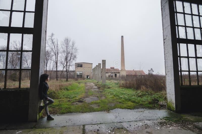 Schönes junges goth Mädchen, das in verlassenem Fabrikgebäude steht stockfotos