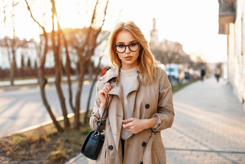 Schönes junges Hippie-Mädchen mit Sonnenbrille in einem Mantel mit stockbild