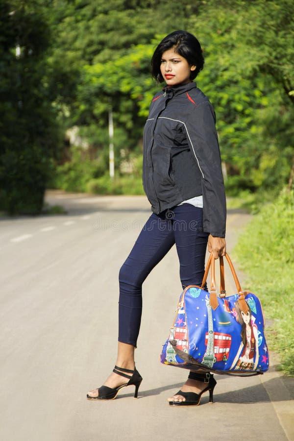 Schönes junges indisches Mädchen mit den kurzen Haaren, die Gepäck- oder Reisetaschenstellung an der Straßenseite, Pune halte stockfotos