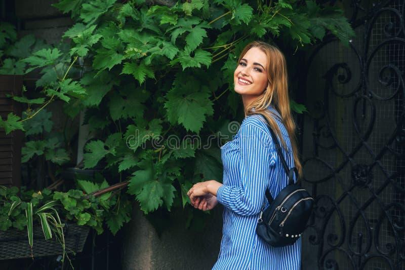 Schönes junges lächelndes Mädchen auf der Stadtstraße stockfoto