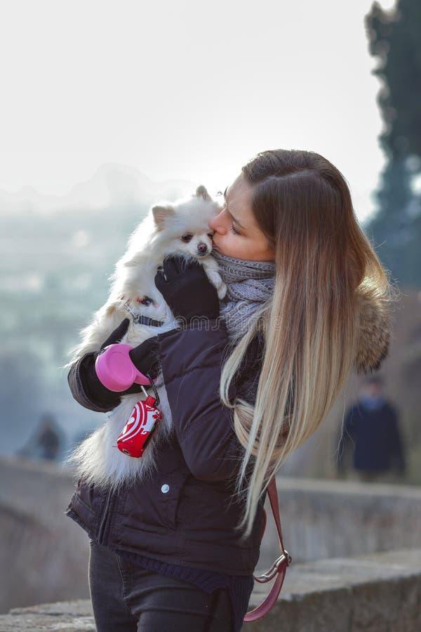 Schönes junges lächelndes Mädchen schlendert mit kleinem weißem Hund Deutscher zwergartiger Spitz pomeranian stockbild