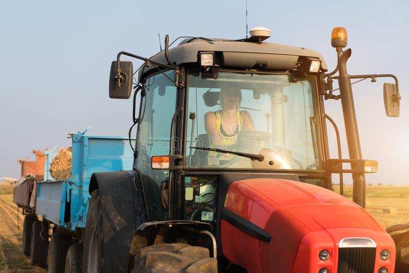Schönes, junges Landwirtmädchen fährt Traktor stockfotografie