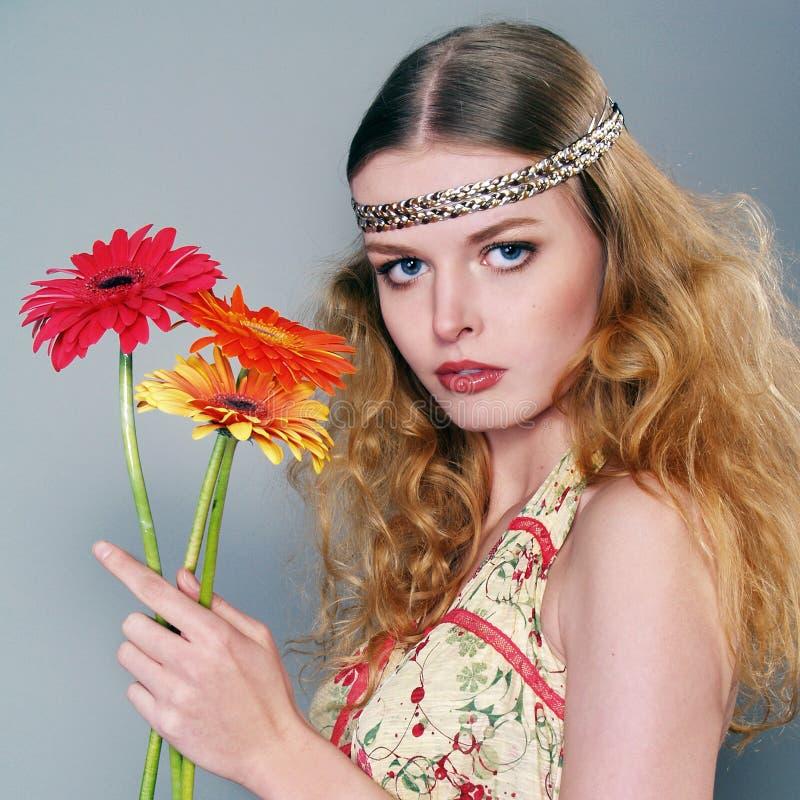 Schönes junges langhaariges Mädchen mit Blumen stockbild