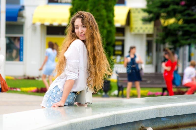 Schönes junges Mädchen überprüft Passanten durch Brunnen im Park stockfotografie