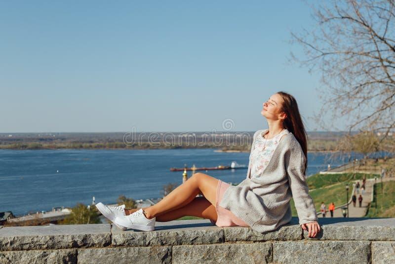 Schönes junges Mädchen, das auf dem die Wolga-Damm sitzt stockfotografie