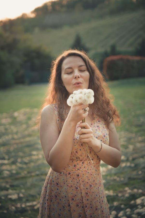 Schönes junges Mädchen, das auf dem Löwenzahngebiet im warmen Sonnenuntergang des schönen Frühlinges spielt stockfotos