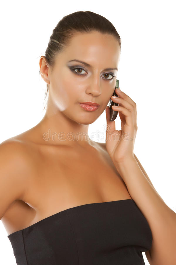 Schönes junges Mädchen, das auf einem Mobile getrennt auf Weiß spricht stockbild
