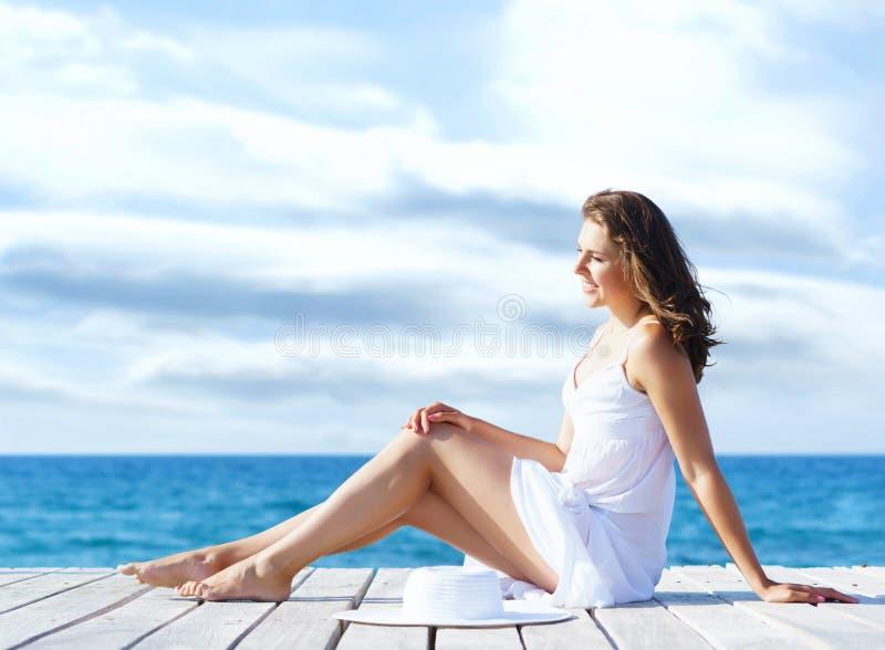 Schönes, junges Mädchen, das auf einem Pier in einem weißen Kleid sitzt Sommer, Ferien und reisendes Konzept lizenzfreie stockfotografie
