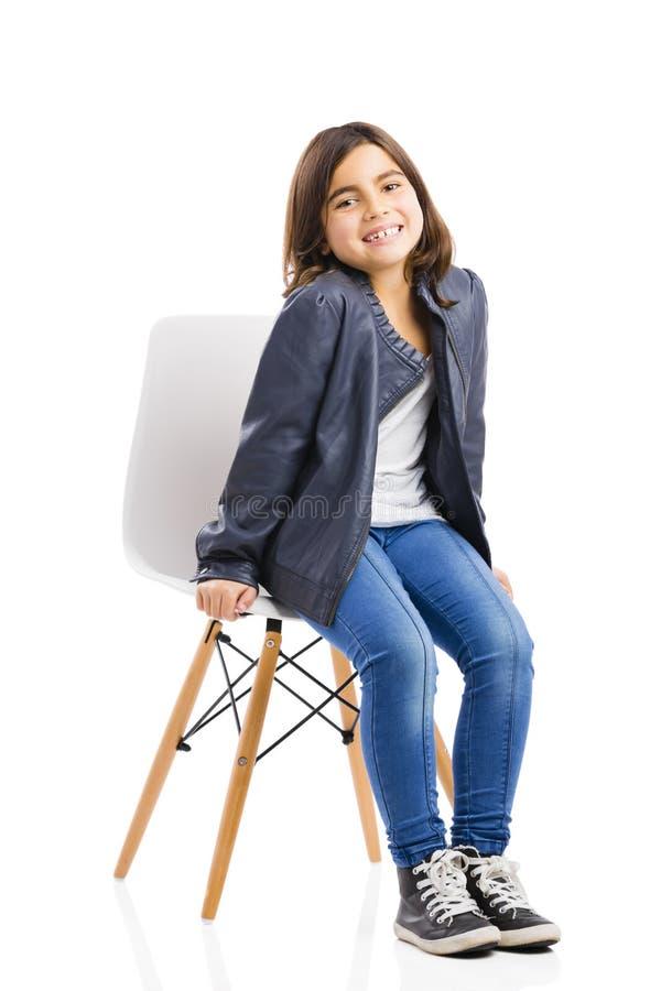 Schönes junges Mädchen, das auf einem Stuhl sitzt lizenzfreies stockbild