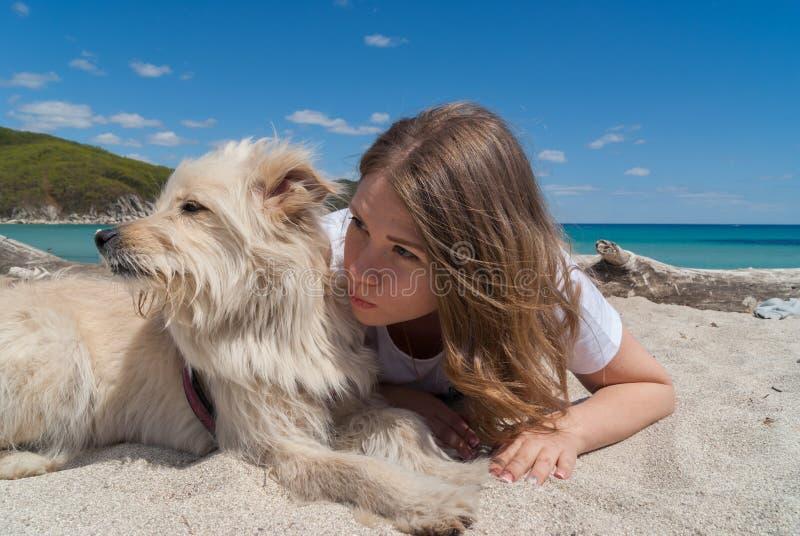 Schönes junges Mädchen, das auf Sandstrand mit ihrem Hund am sonnigen Tag liegt stockbild