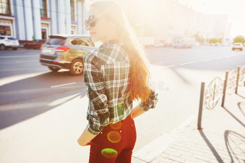Schönes junges Mädchen, das auf sonniger Straße lächelt stockfotos
