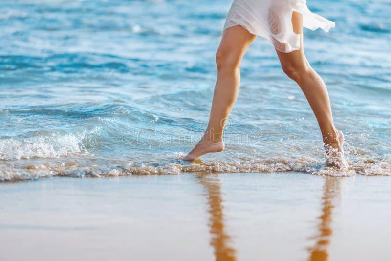 Schönes junges Mädchen, das barfuß auf dem Strand in das Wasser läuft Mädchen, das barfuß in das Wasser bei Sonnenuntergang geht lizenzfreie stockbilder