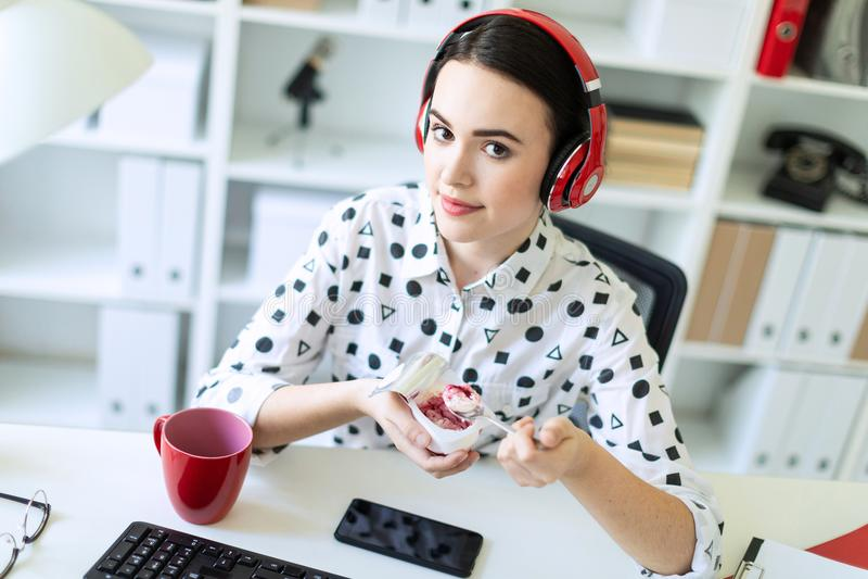 Schönes junges Mädchen, das in den Kopfhörern am Schreibtisch im Büro isst Jogurt mit roter Füllung sitzt stockfotografie