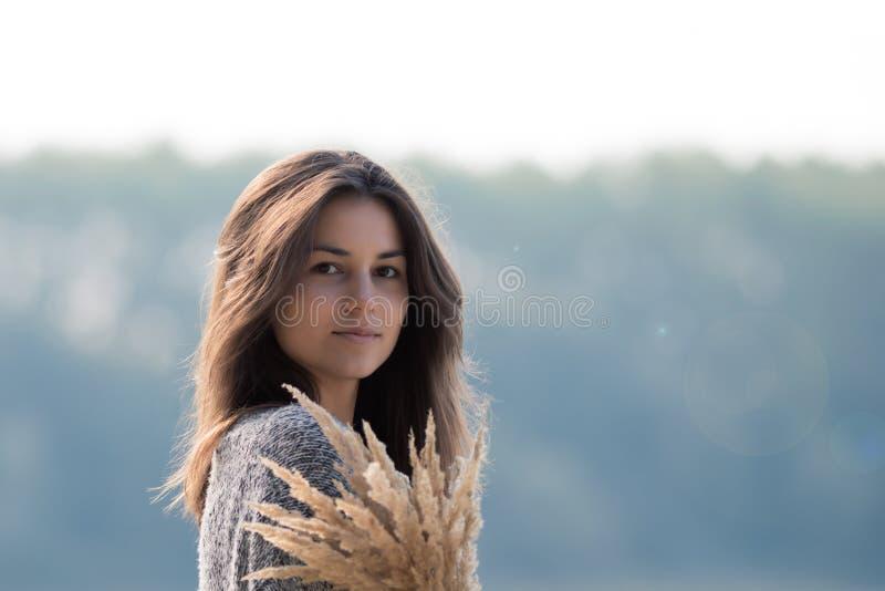 Schönes junges Mädchen, das den See bereitsteht lizenzfreies stockbild