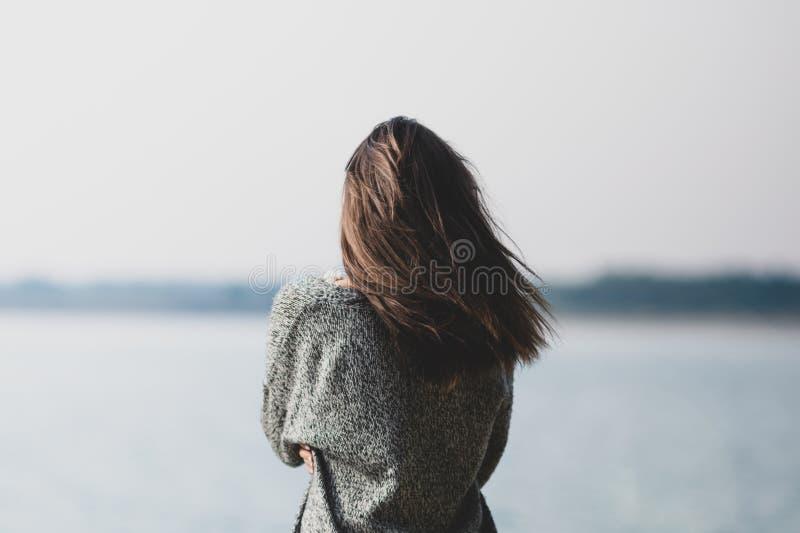Schönes junges Mädchen, das den See bereitsteht stockfoto