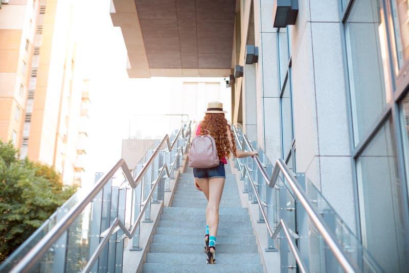 Schönes junges Mädchen, das durch Schritte in einem Stadthintergrund geht lizenzfreie stockfotografie