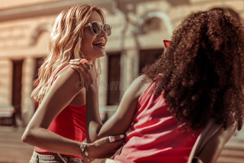 Schönes junges Mädchen, das ein Lachen mit ihrem afroen-amerikanisch Freund teilt lizenzfreie stockfotografie