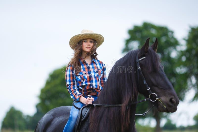 Schönes junges Mädchen, das ein Pferd in der Landschaft reitet stockfotos
